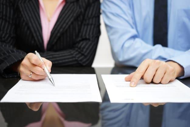 Homem e mulher analisando contratos de tradução jurídica para negócios.