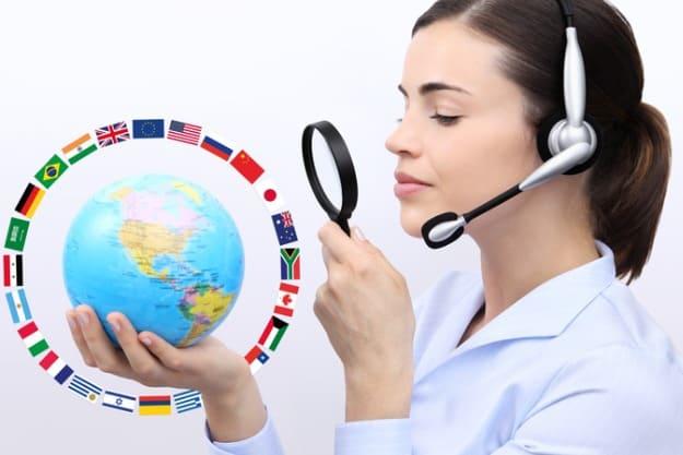Profissional em tradução juramentada olhando globo terrestre e sua variação de idiomas com lupa.